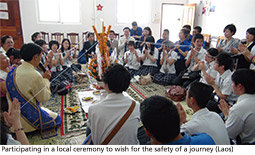 Participating in a local ceremony to wish for the safety of a journey (Laos)